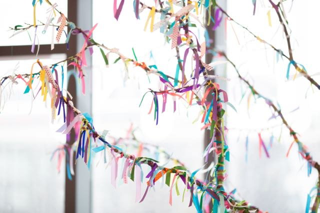 A tree branch is adorned with colourful ribbons representing each birth at the TBC.
