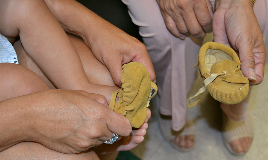 Midwife puts moccasin on baby's foot