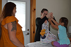 Photo of midwife weighing baby with family at Six Nations birth centre.