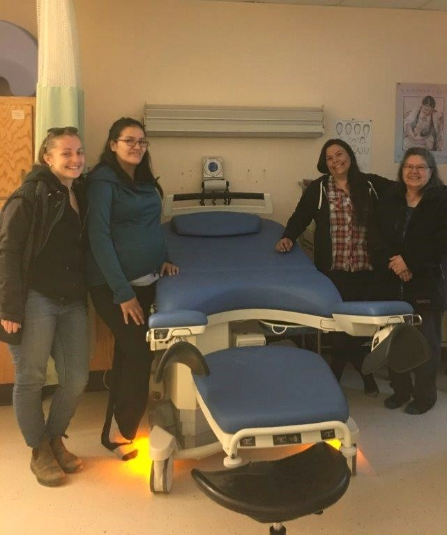 Care providers and expectant parent pose beside new birth bed.